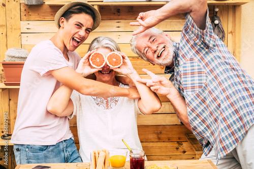 Fényképezés Senior couple grandparents with teenager nephew having fun at breakfast