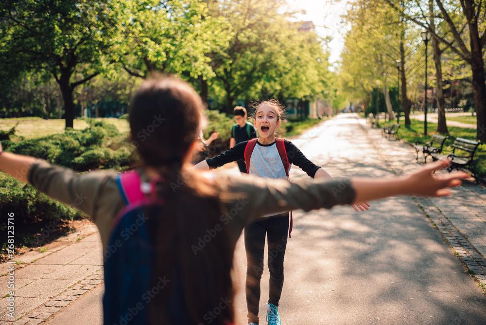 Fototapeta Schoolgirls meet again on first day of school