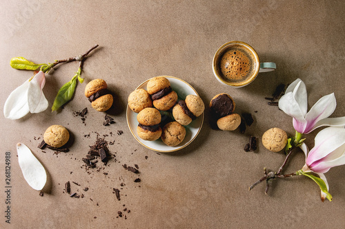 Foto Baci di dama homemade italian hazelnut biscuits cookies with chocolate cream served in ceramic plate with cup of espresso coffee and magnolia flowers over brown texture background