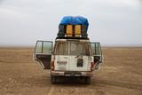 Fototapeta Sawanna - stojący samochód terenowy z otwartymi drzwiami podczas postoju na pustkowiu w pustynnym terenie