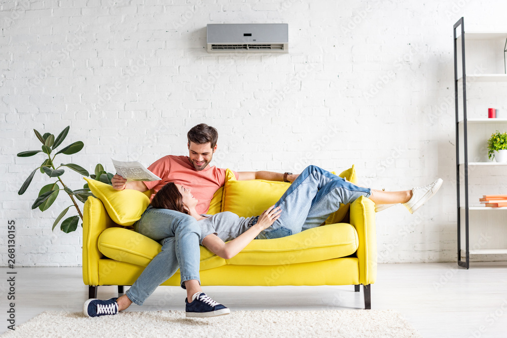 Fototapeta happy man with smiling girlfriend relaxing on yellow sofa under air conditioner at home
