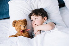 Cute Kid Lying On White Pillow In Bed And Looking At Teddy Bear