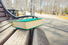 Green Book Lying On A Bench In The Park. The Concept Of Summer Reading, Outdoor Recreation With A Book. Bright Sunny Day.