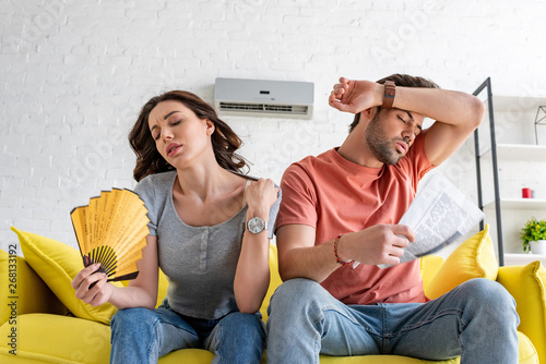 Fototapeta pretty woman with hand fan and handsome man with newspaper suffering from heat at home obraz