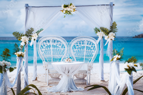 Leinwand Poster Beach wedding arch gazebo ceremonial decorated with white flowers on a tropical grand anse sand beach