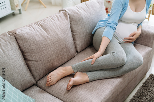 Obraz close up focus on legs cramps during pregnancy. Pregnant unrecognized woman gets feet hurting painful resting at home on couch sofa. asian lady in casual wear future mom massage feet baby in belly - fototapety do salonu