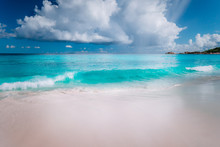 Beautiful White Wave Rolling Towards Tropical Sandy Beach. Gorgeous Fluffy Clouds Above Blue Sea. Seychelles Grand Anse, La Digue, Seychelles