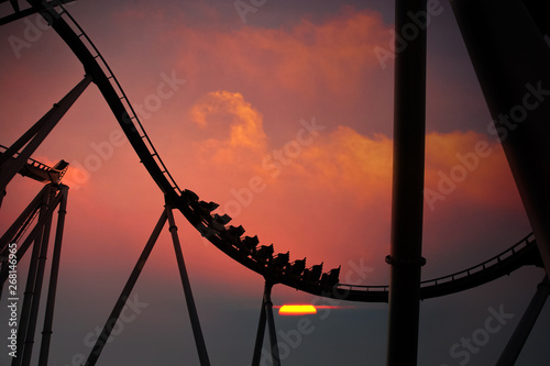 Canvas Prints Amusement Park Silhouette of people having fun on a roller-coaster in an amusement park at sunset. Adrenalin concept.