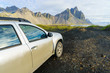 Dirty silver color car on countryside road in Vesturhorn Mountain in summer morning. Stokksnes, Iceland, Northern Europe, Scandinavia. Scenic beautiful nature landscape. Popular tourist attraction.