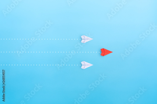 Photo  Leadership concept with red paper plane leading among white on blue background,