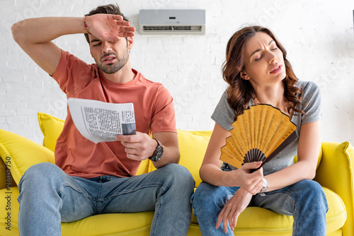 Obraz na płótnie exhausted man and woman sitting on sofa and suffering from heat at home