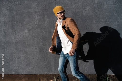 Valokuva  Portrait of handsome bearded man dressed in fashionable clothes standing on stre