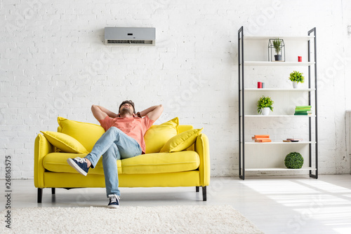 Fototapeta  young man sitting on yellow sofa under air conditioner in spacious apartment