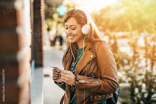 Obraz na plátne Happy young adult woman with headphones on her head standing in front of atm machine, smiling and holding credit or debit card