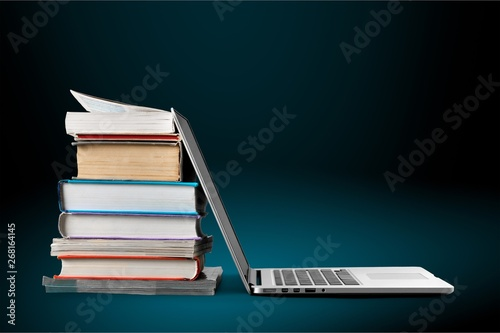 Stack of books with laptop on table - 268164145