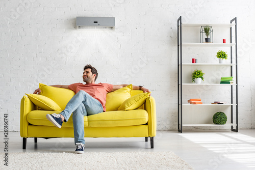 Fotografie, Obraz  smiling handsome man sitting on yellow sofa under air conditioner at home