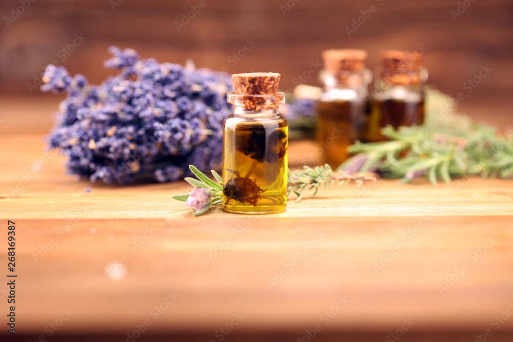 Fototapety, obrazy: essential lavender oil in a glass bottle on a background of fresh flowers