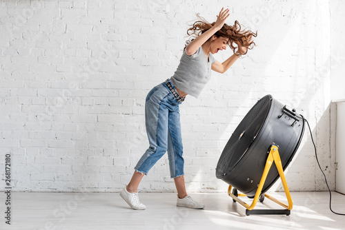 Cuadros en Lienzo  excited young woman in blue jeans standing with raised hands in front of blowing