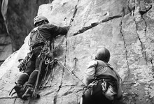 Rock Climbers On A Rock Wall Closeup. Climbing Gear And Equipment. Black And White.