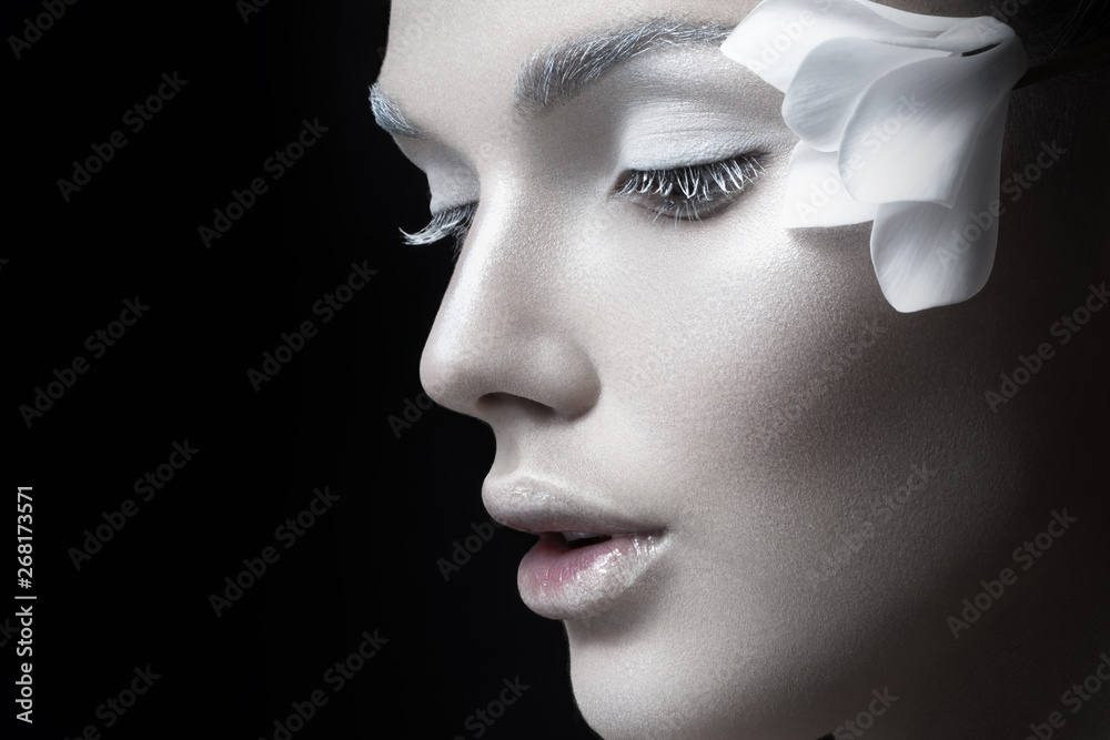 Fototapety, obrazy: Beauty portrait. Tender girl with fragile white makeup, anf flowers near ear, looking down, Concept salon makeup, cosmetics, isolated on black background.