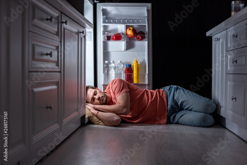 Leinwand Poster exhausted man sleeping near open refrigerator on kitchen floor