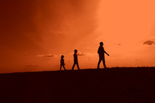 Father, Son And Daughter Are Walking In Nature At Sunset