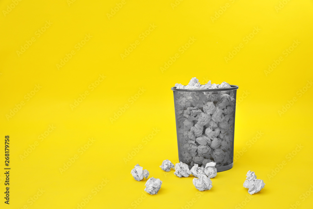 Fototapeta Metal bin with crumpled paper on color background, space for text