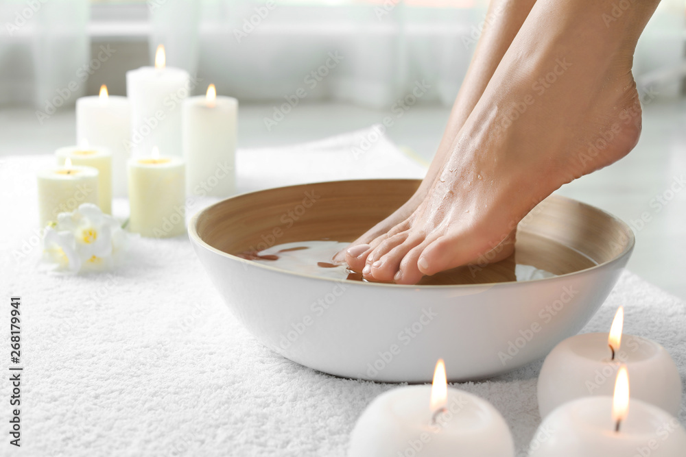 Fototapeta Woman soaking her feet in dish indoors, closeup with space for text. Spa treatment
