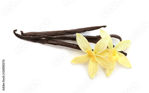 Fotografía  Aromatic vanilla sticks and flowers on white background
