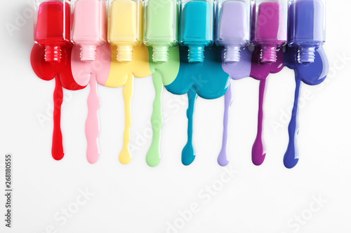 Spilled colorful nail polishes and bottles on white background, top view
