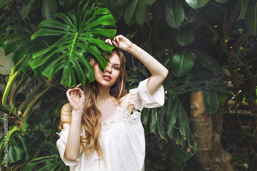 Obraz Young beautiful happy blonde girl model on tropical plants background with green leaf - fototapety do salonu