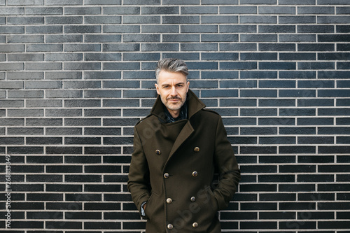 Successful trendy man with grey hair and bristle over brick wall. - 268183349
