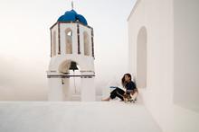 Girl Resting Near Orthodox Church At Santorini, Greece