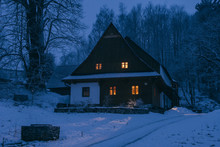 Traditional Log Cabin In Snow Covered Landscape