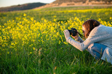 Teenage Girl Shooting Yellow Mustard Flowers In A Field