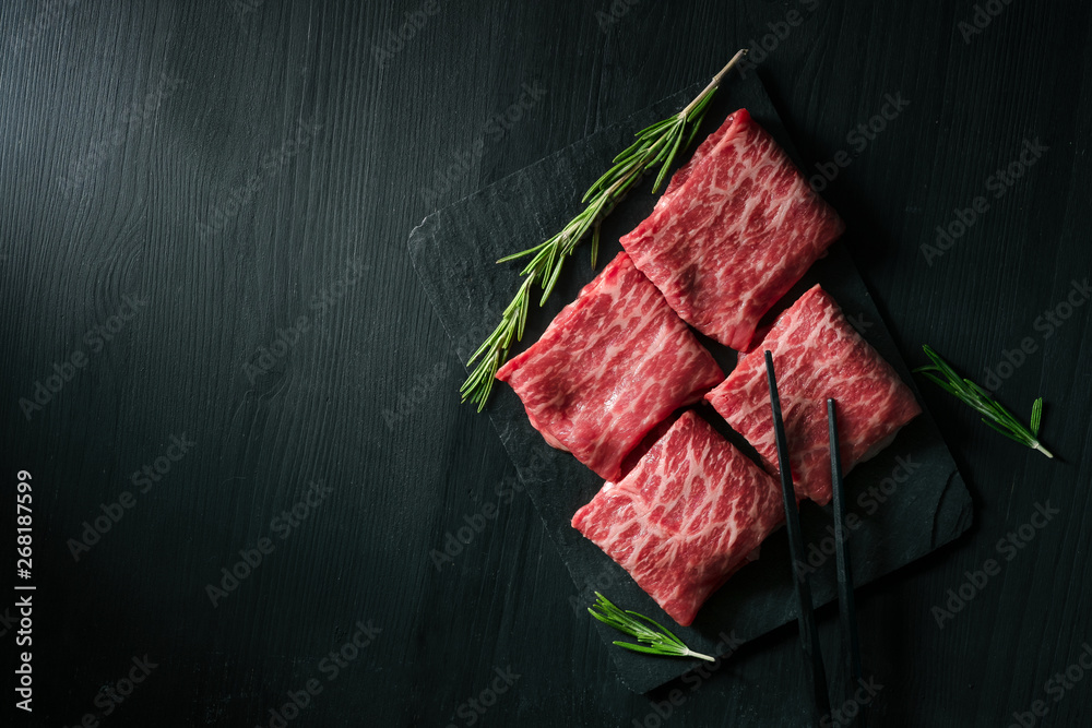Fototapeta Sliced wagyu marbled beef for yakiniku on plate on black background, Premium Japanese meat, top view and copy space