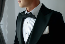 Elegant Man Wearing Black Tie Suit With White Shirt And Silk Bow Tie And White Handkerchief Or Pocket Square, Sartorial Accessories For Formal Attire, A Classy Groom Or A Sophisticated Business Person