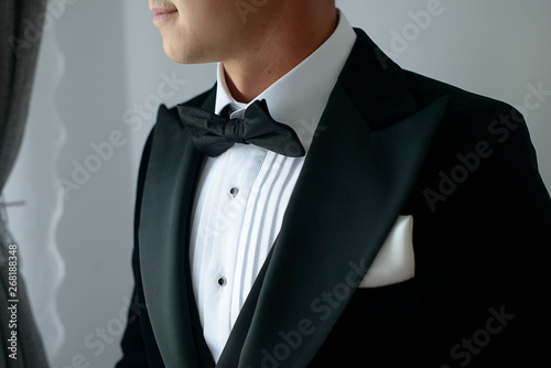 Obraz na płótnie Elegant man wearing black tie suit with white shirt and silk bow tie and white h