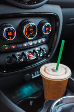 An Iced Coffee Drink Placed In A Cup Holder Inside A Car.