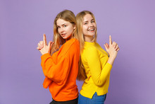 Two Young Blonde Twins Sisters Girls In Colorful Clothes Standing Back To Back, Keeping Fingers Like Gun Isolated On Pastel Violet Blue Background. People Family Lifestyle Concept. Mock Up Copy Space.