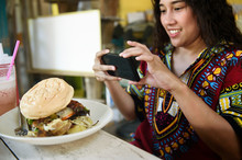 Woman Taking A Photo Of A Huge Burger In A Colourful Cafe