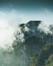 Mountain Peeking Through The Clouds.