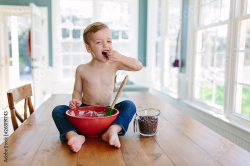 Young boy sitting on a kitchen table boy eating chocolate chips and cookies