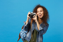 Young African American Girl Teen Student In Denim Clothes Backpack Hold Camera Isolated On Blue Wall Background Studio Portrait. Education In High School University College Concept. Mock Up Copy Space