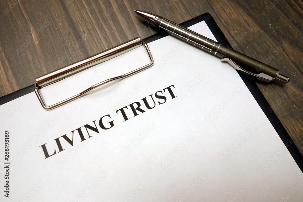 Fototapeta Clipboard with living trust and pen on desk