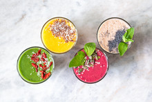 Healthy Vegan Smoothies With Forest Fruits, Bananas, Spinach, Coconut Milk, Pineapple, Kiwi, Mint, Turmeric, Chia, Flax Seeds, Goji Berry, And Coconut Flakes