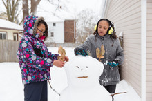 Sisters Building A Snowman Out...