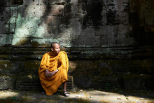 Monk In Orange Clothes Sitting...