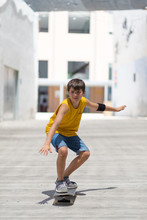 Front View Of Cheerful Skater Boy Riding On The City In A Sunny Day
