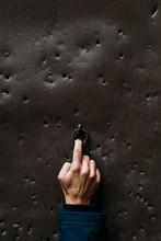 Hand Touching A Door Knocker
